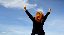 Woman jumping up and raising hands in air --